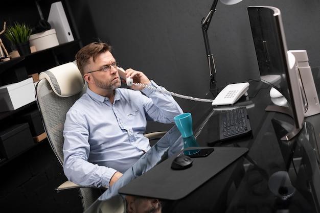 Homem de negócios sério trabalhando no escritório, na mesa do computador e falando em telefone fixo