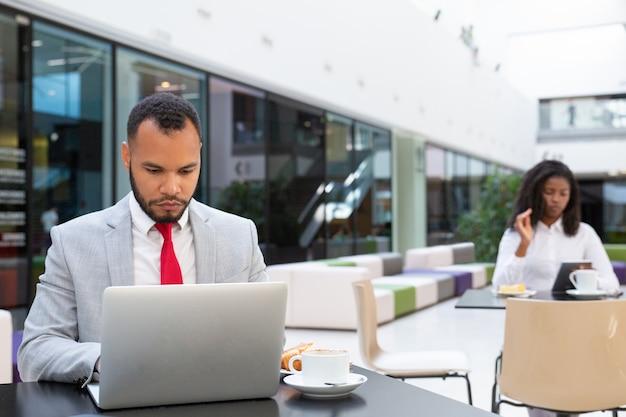 Homem de negócios sério trabalhando no laptop enquanto bebe café