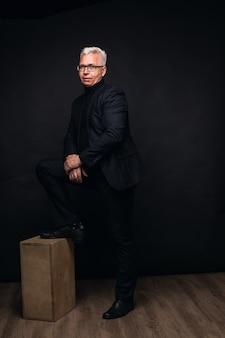 Homem de negócios sério usando óculos com cabelo branco para a câmera e uma expressão focada em um fundo preto de estúdio