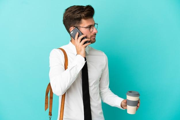 Homem de negócios sobre fundo isolado segurando café para levar e um celular