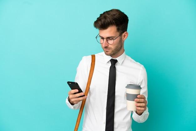 Homem de negócios sobre um fundo isolado segurando um café para levar e um celular