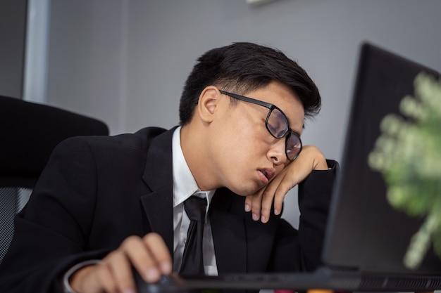 Homem de negócios sonolento na mesa de trabalho entre o uso de computador portátil