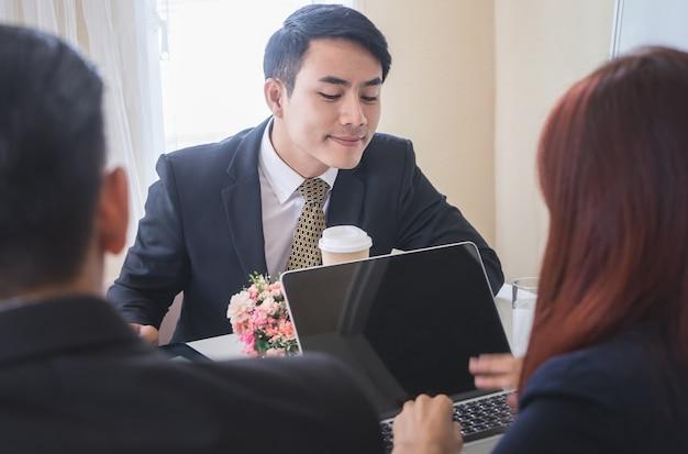 Homem de negócios sorrateiro está olhando para outras pessoas computador