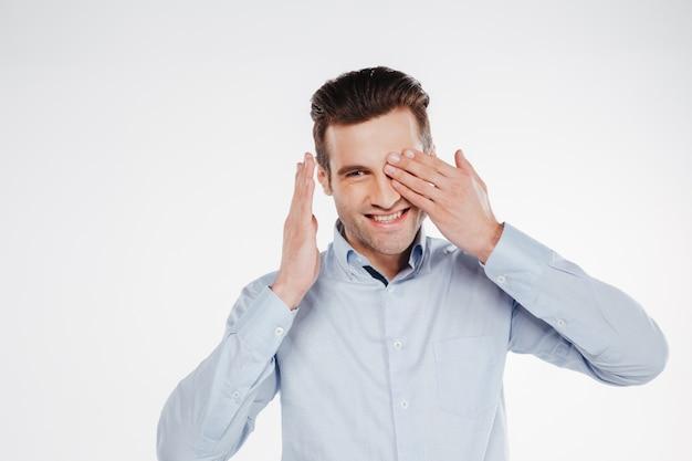 Homem de negócios sorridente, cobrindo um olho
