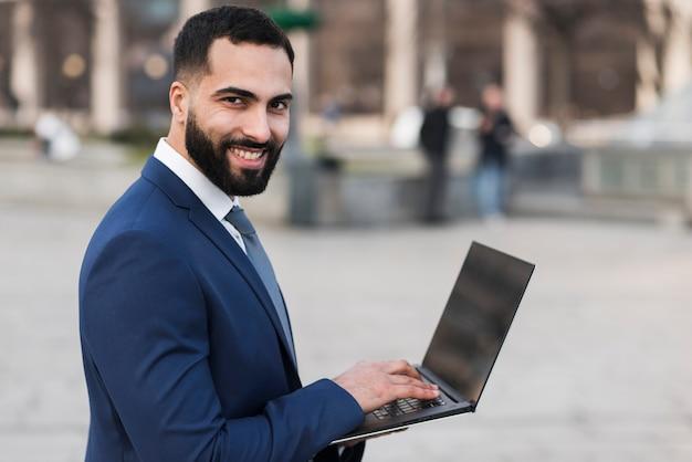 Homem de negócios sorridente com laptop