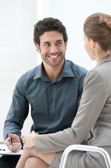 Homem de negócios sorridente conversando com seu colega durante uma reunião informal no escritório