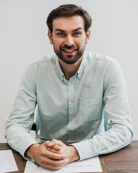 Homem de negócios sorridente de vista frontal em seu escritório