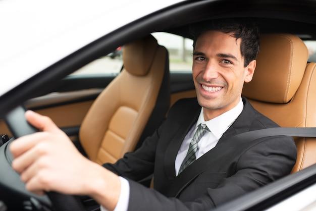 Homem de negócios sorridente dirigindo seu novo carro branco
