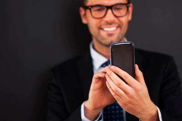 Homem de negócios sorridente enviando mensagens de texto no telefone inteligente