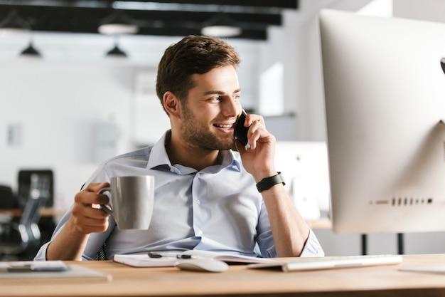 Homem de negócios sorridente falando por smartphone e bebendo café enquanto está sentado à mesa no escritório