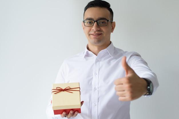 Homem de negócios sorridente segurando a caixa de presente e mostrando o polegar para cima