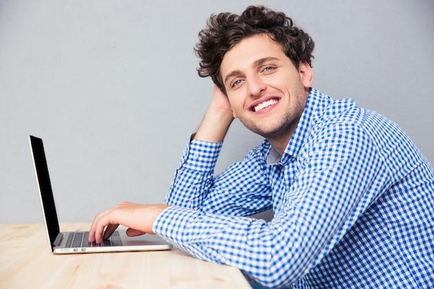 Homem de negócios sorridente sentado à mesa com um laptop