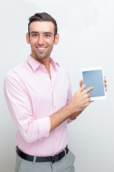 Homem de negócios sorrindo mostrando tela de tabuleta