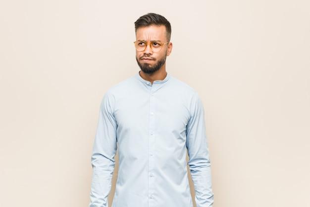 Homem de negócios sul-asiático jovem confuso, sente-se em dúvida e inseguro.