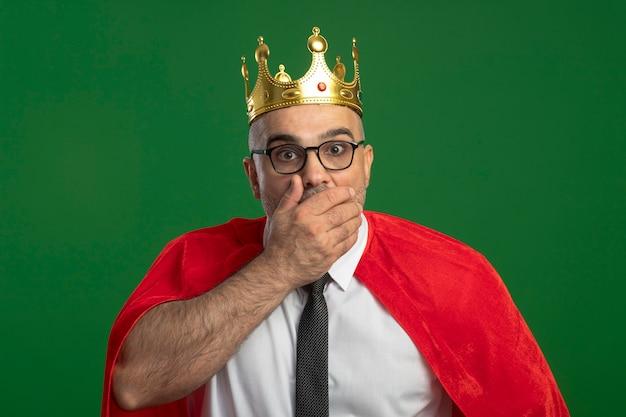 Homem de negócios super-herói com capa vermelha e óculos com coroa, olhando para a frente, maravilhado e surpreso, cobrindo a boca com a mão em pé sobre a parede verde