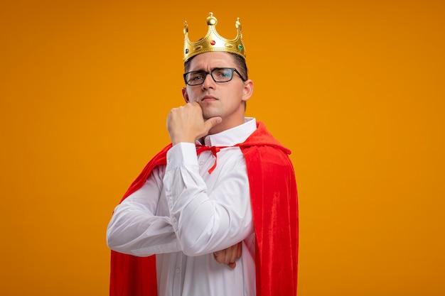 Homem de negócios super-herói com capa vermelha e óculos usando coroa, olhando para a câmera com a mão no queixo com expressão séria e confiante em pé sobre um fundo laranja