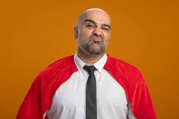 Homem de negócios super-herói com capa vermelha olhando para a frente com uma expressão triste e descontente em pé na parede laranja
