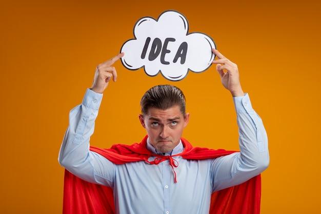 Homem de negócios super-herói com capa vermelha segurando um cartaz de balão com a ideia da palavra na cabeça, parecendo confuso em pé sobre um fundo laranja