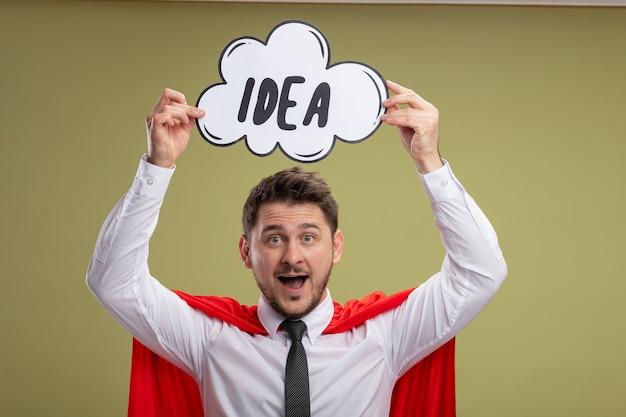 Homem de negócios super-herói com capa vermelha segurando um cartaz de bolha do discurso com a ideia da palavra na cabeça e sorrindo com uma cara feliz em pé sobre um fundo verde