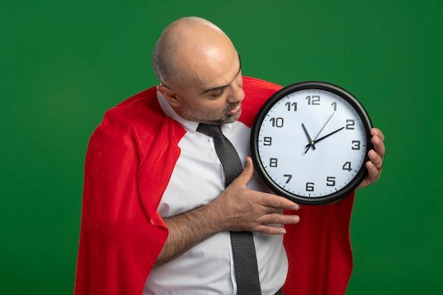 Homem de negócios super-herói com capa vermelha segurando um relógio de parede olhando para ele e ficando louco de espanto e surpresa em pé sobre a parede verde