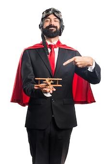 Homem de negócios super-herói segurando um avião de brinquedo de madeira
