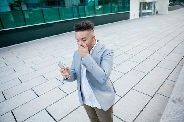 Homem de negócios surpreendido que olha a tela do smartphone