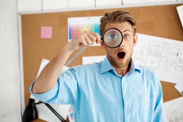 Homem de negócios surpreendido seguro considerável novo que está sobre a placa da cortiça através da lente de aumento. interior de escritório moderno branco