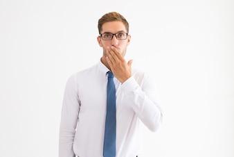 Homem de negócios surpreso cobrindo a boca com a mão