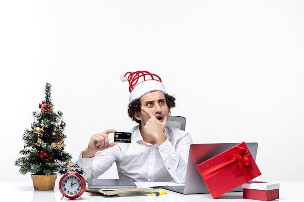 Homem de negócios surpreso com chapéu de papai noel e segurando o cartão do banco, olhando algo com cuidado no escritório em fundo branco