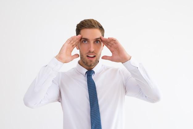 Homem de negócios surpreso tocando templos com a boca aberta