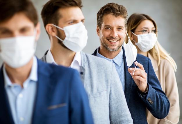 Homem de negócios tirando sua máscara facial de proteção e olhando para a câmera com membros da equipe em pé na fila no escritório