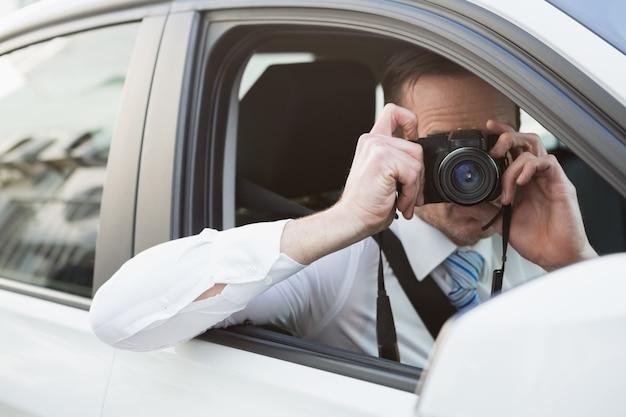 Homem de negócios tomando uma foto enquanto está sentado no assento do motorista