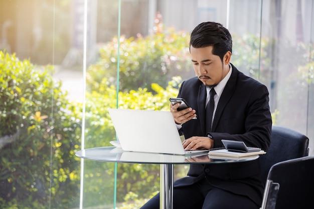 Homem de negócios, trabalhando com smartphone e computador portátil