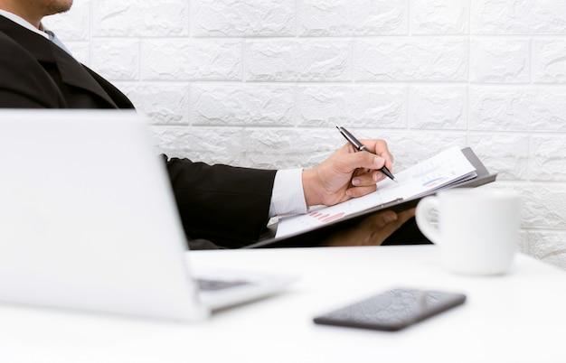 Homem de negócios, trabalhando em documentos olhando café computador e telefone em cima da mesa