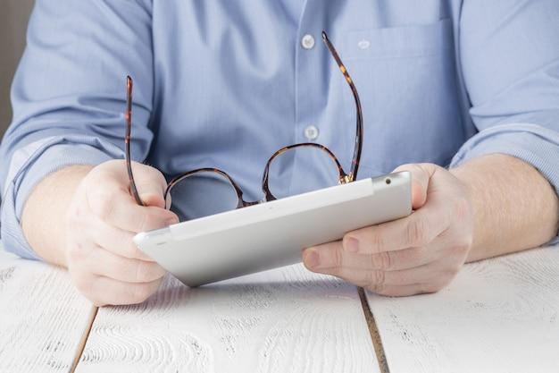 Homem de negócios, trabalhando em tablet digital no escritório ou em casa