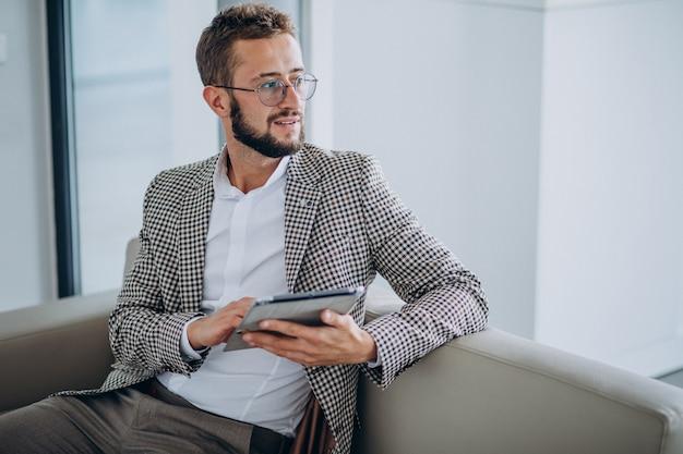 Homem de negócios, trabalhando em um tablet e sentado no sofá