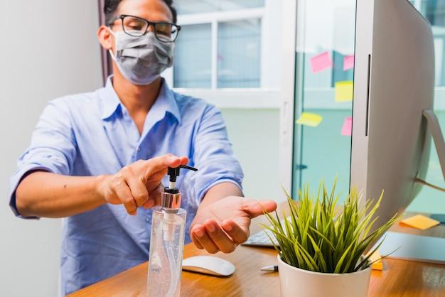 Homem de negócios, trabalhando no escritório em casa, ele coloca o coronavírus em quarentena, usando uma máscara protetora e limpando as mãos com gel desinfetante