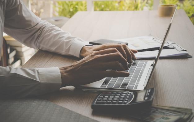 Homem de negócios, trabalhando no laptop e calculadora