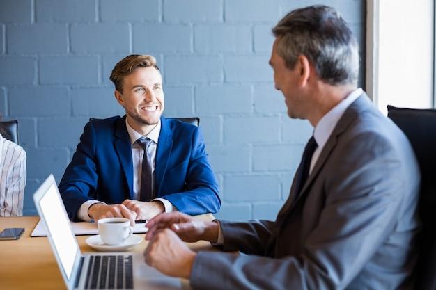 Homem de negócios, trabalhando no laptop em uma sala de conferências durante reunião no escritório