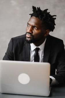 Homem de negócios, um afro-americano de terno trabalha em um laptop
