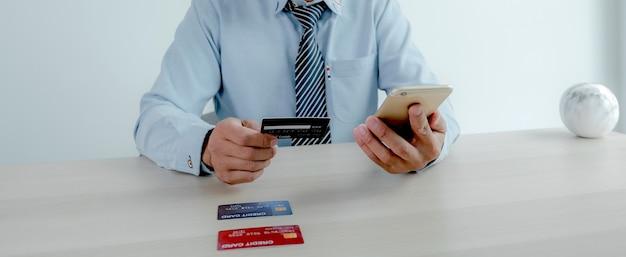Homem de negócios usa cartão de crédito para compras online de casa com laptop, comércio eletrônico de pagamento.