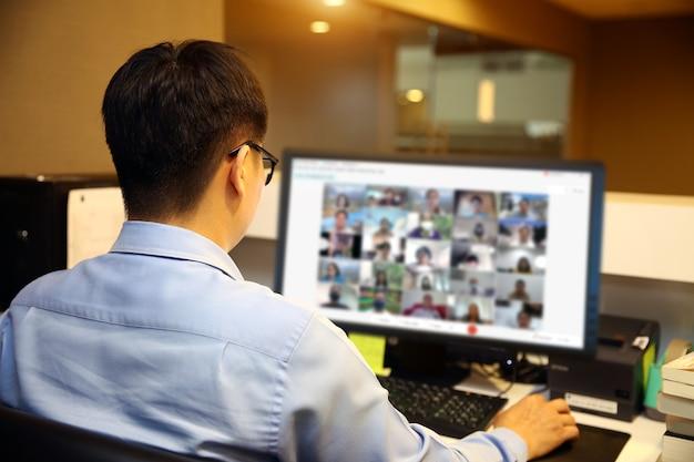 Homem de negócios usa computador para reunião de equipe com programa de videochamada.