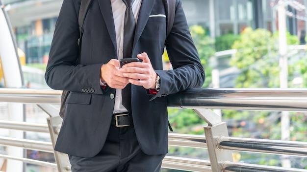 Homem de negócios usa telefone inteligente na suíte de pano inteligente na cidade ao ar livre.