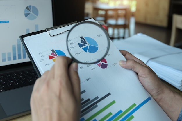 Homem de negócios usando a ampliação para revisar o balanço anual com o uso de computador laptop