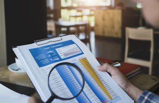Homem de negócios usando a ampliação para revisar o pedido de empréstimo para auditar os números dos empréstimos