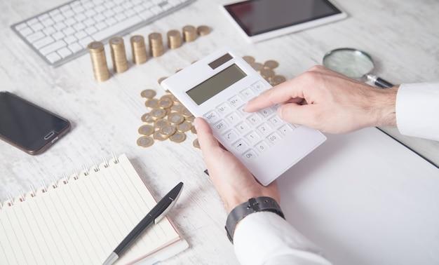 Homem de negócios usando a calculadora com moedas na mesa.