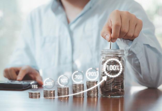 Homem de negócios usando a calculadora e colocando a moeda no frasco de economia com porcentagem do círculo virtual carregando no empilhamento de moedas, economia de dinheiro do depósito e conceito de crescimento do lucro do negócio.