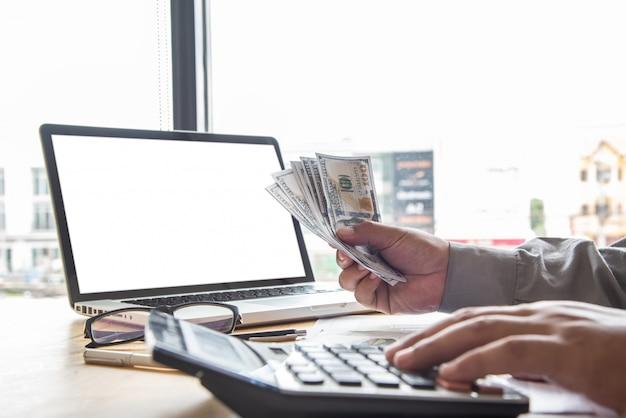 Homem de negócios usando a calculadora e segurando o dinheiro