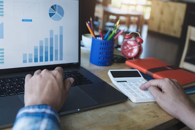 Homem de negócios usando a calculadora para revisar o balanço anual com caneta e usando o laptop