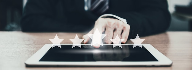 Homem de negócios usando aplicativo para tablet com gráfico de ícone de cinco estrelas para dar a taxa de atendimento ao cliente